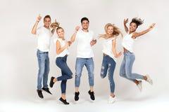 Grupo de gente sonriente que salta, divirtiéndose junto foto de archivo