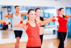 Grupo de gente sonriente que se resuelve con pesas de gimnasia Foto de archivo libre de regalías