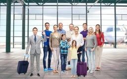 Grupo de gente sonriente sobre el terminal de aeropuerto Imágenes de archivo libres de regalías