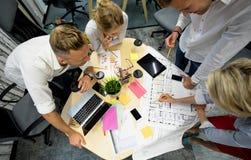 Grupo de gestores de projeto em torno da tabela imagens de stock royalty free