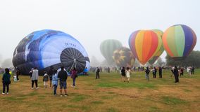 Grupo de globos del aire caliente en el festival de aerostación, cubierto en niebla imagenes de archivo