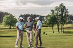 Grupo de golfistas que detienen a los clubs y que hablan mientras que se coloca en hierba verde imagenes de archivo