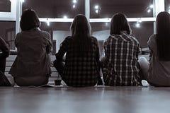 Grupo de hembras que miran en la ventana Imagen de archivo libre de regalías