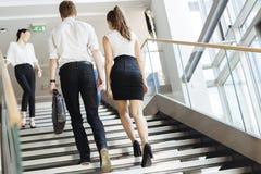 Grupo de hombre de negocios que camina y que toma las escaleras Imágenes de archivo libres de regalías