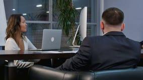 Grupo de hombres de negocios acertados que hablan junto mientras que trabaja alrededor de una tabla en una sala de reunión de la  almacen de video