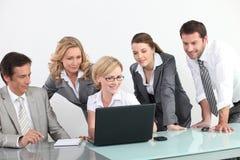 Grupo de hombres de negocios delante de una computadora portátil Fotos de archivo libres de regalías