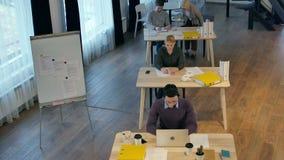 Grupo de hombres de negocios jovenes que trabajan y que comunican junto en oficina creativa almacen de metraje de vídeo