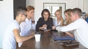 Grupo de hombres de negocios jovenes que usan la tableta en cafetería almacen de video
