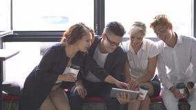 Grupo de hombres de negocios jovenes que usan la tableta en cafetería Cámara lenta almacen de metraje de vídeo