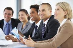 Grupo de hombres de negocios que escuchan el colega que dirige la reunión de la oficina fotos de archivo