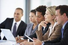 Grupo de hombres de negocios que escuchan el colega que dirige la reunión de la oficina imagenes de archivo
