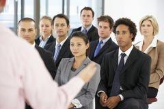 Grupo de hombres de negocios que escuchan el Presidente que da la presentación foto de archivo
