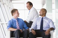 Grupo de hombres de negocios que hablan en pasillo Imagenes de archivo