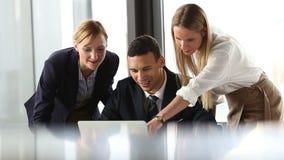 Grupo de hombres de negocios que miran el ordenador portátil y la discusión almacen de metraje de vídeo