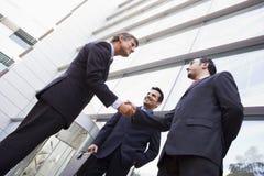 Grupo de hombres de negocios que sacuden las manos fuera de la oficina Fotografía de archivo libre de regalías