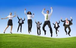 Grupo de hombres de negocios que saltan en la colina Imágenes de archivo libres de regalías