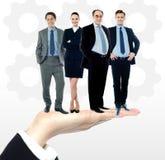 Grupo de hombres de negocios que se colocan en la palma imagenes de archivo