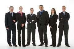 Grupo de hombres de negocios que se colocan en una línea Foto de archivo