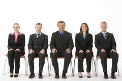 Grupo de hombres de negocios que se sientan en una línea Fotografía de archivo libre de regalías