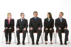 Grupo de hombres de negocios que se sientan en una línea Imágenes de archivo libres de regalías