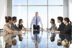 Grupo de hombres de negocios que tienen reunión del Consejo alrededor de la tabla de cristal foto de archivo