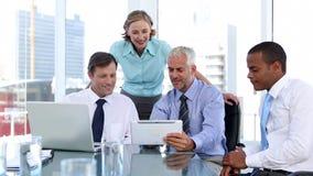 Grupo de hombres de negocios que usan el ordenador portátil y la tableta almacen de video