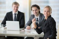 Grupo de hombres de negocios sonrientes en el escritorio de oficina moderno imagen de archivo