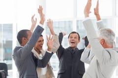 Grupo de hombres de negocios sonrientes que aumentan sus manos Fotografía de archivo
