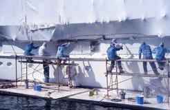 Grupo de hombres en los guardapolvos que pintan el barco. Fotografía de archivo