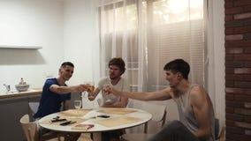 Grupo de hombres jovenes con los vidrios que beben en la cocina metrajes