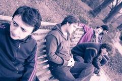 Grupo de hombres jovenes en banco Imagenes de archivo