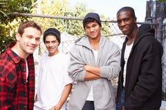 Grupo de hombres jovenes en el ambiente urbano que hace una pausa el FE imagen de archivo libre de regalías