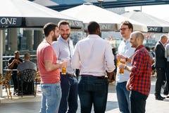 Grupo de hombres jovenes que beben en una barra del área de embarque Imágenes de archivo libres de regalías