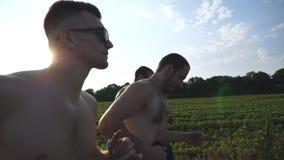 Grupo de hombres jovenes que corren a lo largo del camino rural sobre campo con la llamarada del sol en el fondo Perfil de los at Fotos de archivo