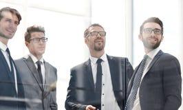 Grupo de hombres de negocios confiados que se colocan en la oficina imagen de archivo libre de regalías