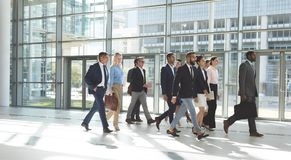 Grupo de hombres de negocios diversos que caminan junto en oficina del pasillo fotos de archivo libres de regalías