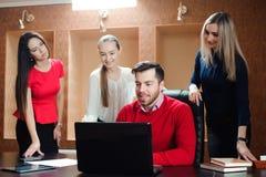 Grupo de hombres de negocios jovenes inspirados sonrientes que trabajan junto en oficina imagenes de archivo
