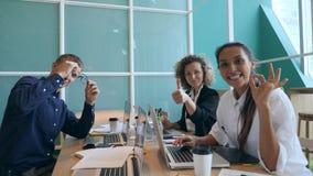 Grupo de hombres de negocios jovenes de la raza mixta que muestran los pulgares para arriba en oficina Concepto de Co-trabajo de  metrajes