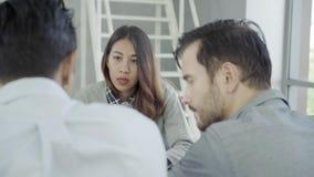 Grupo de hombres de negocios ocasional vestidos que discuten ideas en la oficina almacen de metraje de vídeo