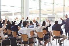 Grupo de hombres de negocios que aumentan las manos en el seminario en la conferencia fotografía de archivo libre de regalías