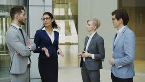 Grupo de hombres de negocios que hablan en oficina moderna Equipo de hombres de negocios y de empresarias que discuten y que se c