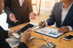 Grupo de hombres de negocios que hacen frente a la discusión de la comunicación sobre analizar informe financiero de los datos en fotos de archivo libres de regalías