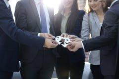 Grupo de hombres de negocios que montan el rompecabezas, ayuda del equipo imagen de archivo libre de regalías