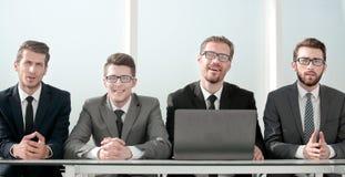 Grupo de hombres de negocios que se sientan en el escritorio imagen de archivo