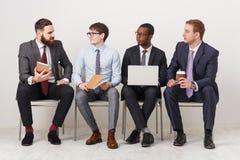 Grupo de hombres de negocios que se sientan en sillas fotografía de archivo libre de regalías