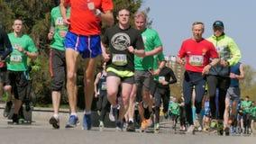 Grupo de hombres y de mujeres de los corredores que corren en la calle de la ciudad