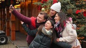 Grupo de homem e de mulheres de sorriso que tomam Selfie fora perto da árvore do Xmas Amigos que têm o divertimento no mercado do filme