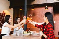 Grupo de homem novo asiático e de mulheres felizes e sorrindo que guardam um cocktail alcoólico para brindar e comemorar no parti fotografia de stock royalty free