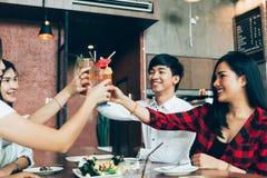 Grupo de homem novo asiático e de mulheres felizes e sorrindo que guardam um cocktail alcoólico para brindar e comemorar no parti imagem de stock