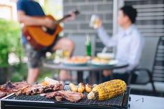 Grupo de homem novo dos amigos dois que aprecia a carne e a guitarra grelhadas do jogo com aumento um o vidro da cerveja para com imagens de stock